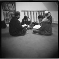 Mosquée Omar (11ème arrondissement), assis  en tailleur, de jeunes adultes récitent le coran.