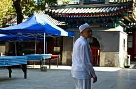 Chine : un homme installe les tables pour la rupture du jeûne dans la cour de la mosquée.