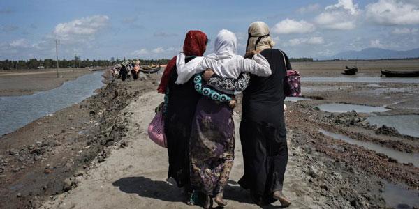Trois femmes rohingyas ayant fui la Birmanie en traversant la rivière Naf marchent vers un camp de réfugiés situé à Teknaf, dans le district de Cox's Bazar, au Bangladesh.  ©Anastasia Taylor-Lind