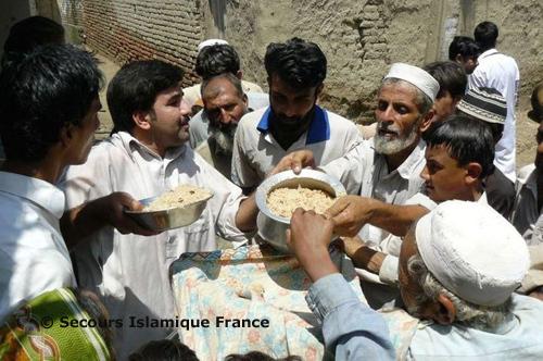 Au centre de la photo (col bleu), Inayat Ur Rehman, le coordonnateur de projets sur place du SIF, distribue les repas.