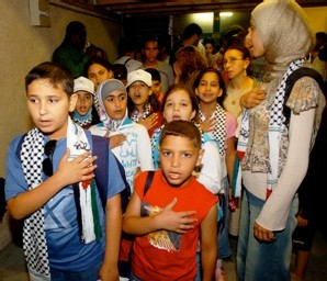 Ali (à gauche) et Khalid (à droite), accompagnés du groupe, chantent l'hymne national palestinien.