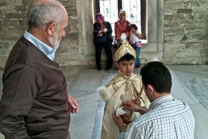A la moquée d'Eyub, à Istanbul, devant son grand-père, un père prépare son enfant avant la circoncision. L'enfant porte la tenue traditionnelle pour ces occasions. © 2011 Michael Fuery - Agence: iStockPhoto.