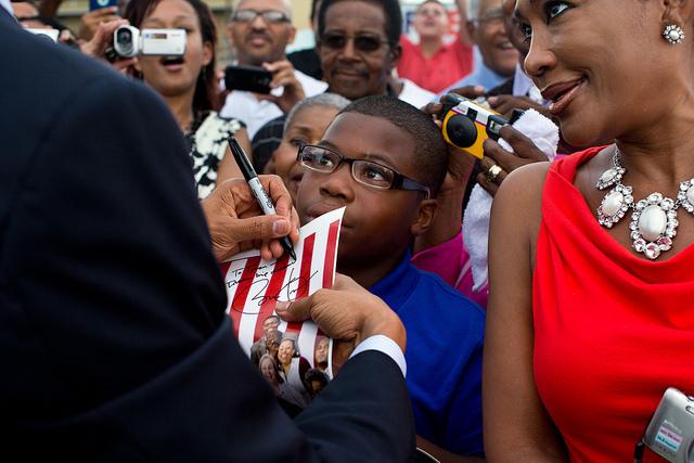 Le président Barack Obama, signant un autographe, sur le tarmac de l'aéroport Louis Armstrong, à la Nouvelle-Orléans, en juillet 2012. (Photo : © Official White House / Pete Souza)