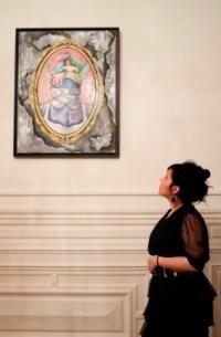 Haquima Akhabach en présence d'un de ses tableaux.