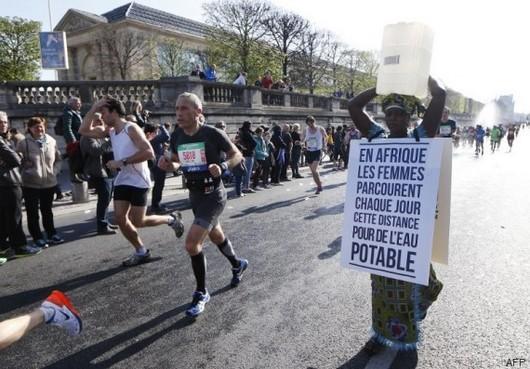 La Gambienne Siabatou Sanneh a pris le départ du marathon de Paris, dimanche 12 avril, avec un bidon sur la tête pour sensibiliser l'opinion publique aux longues distances parcourus en Afrique pour accéder à l'eau. © AFP