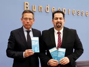 A droite, Aiman Mazyek, président du Conseil central des musulmans d'Allemagne (ZMD), aux côtés de Johannes-Wilhelm Rörig, présentent leur dépliant pour lutter contre les abus sexuels des enfants migrants.