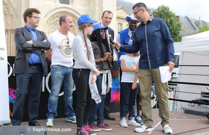 Après une douzaine de dictées des cités, la finale a été organisée à Saint-Denis le 10 juin à l'initiative de l'écrivain Rachid Santaki, ici tendant le micro à quelques uns des lauréats de l'Eurodictée à Saint-Denis.