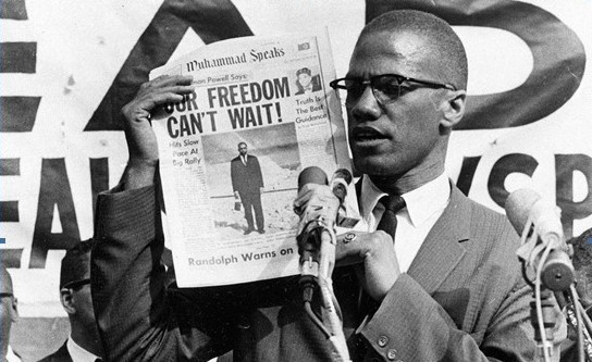 Malcolm X brandissant un exemplaire de Muhammad Speaks, journal de la NOI.