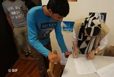 Des réfugiés accueillis dans un foyer du Secours Islamique France (SIF) finalisent leur inscription avant qu'on leur attribue une chambre. (Photo © SIF)