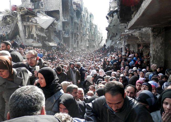 Des centaines de Palestiniens du camp de Yarmouk, en Syrie, se dirigeant vers un point de distribution de nourriture le 31 janvier. © UNRWA