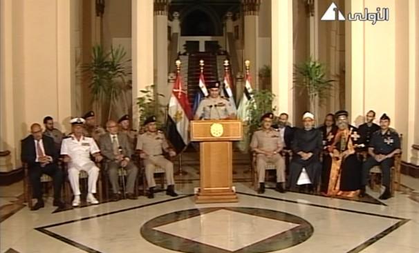 Discours à la nation du général al-Sissi devenu président élu à 98 %, entouré de personnalités militaires, politiques et religieuses, notamment Mohamed El-Baradei (Prix Nobel de la paix, nommé vice-président le 9 juillet mais qui donnera sa démission le 14 août), le cheikh d'Al-Azhar Ahmed El-Tayeb et le pape copte Tawadros II. (Image du 3 juillet 2013, extraite de la télévision d'État égyptienne.)