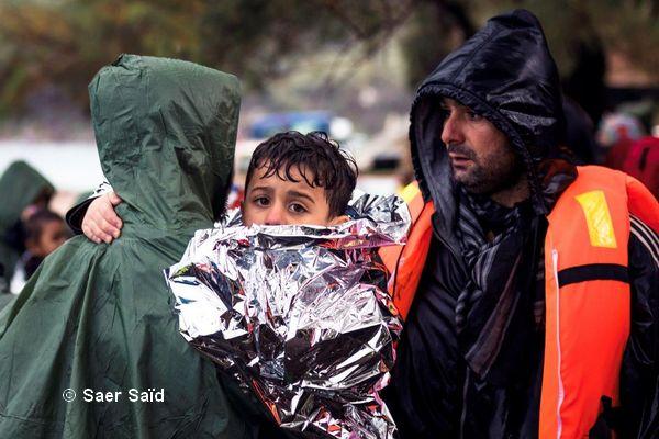 Un enfant trempé, dans une couverture de survie, se réchauffe dans les bras de son père. Lesbos (Grèce), octobre 2015. © Saer Said