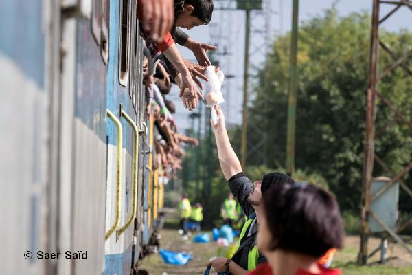 Des bénévoles distribuent des vivres aux réfugiés. Une fois les portes fermées, ils n'ont plus le droit de descendre du train. Zakany (Hongrie), octobre 2015. © Saer Saïd